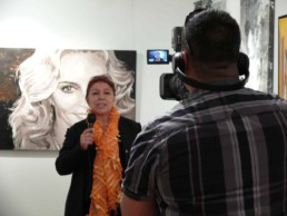 Art Gallery owner Nina Torres interviewed by CNN in front of the Madonna portrait painting by artist Peter Engels