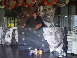 Peter Engels with his presidential portrait paintings of Barack Obama and herman Van Rompuy