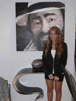 Montana Engels, daughter of Peter Engels, with the Luciano Pavarotti portrait painting