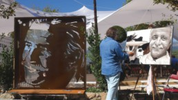 Artist Peter Engels working on the Roger Vergé portrait painting next to his sculpture in rusty corten steel that the mayor of Mougins ordered.