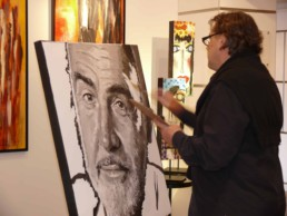 Peter Engels working on the Sean Connery portrait painting on board of the mega yacht Sea Fair during Art Basel Miami