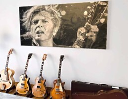 The David Bowie painting in its new home in Monaco in good company of Bowie guitars.